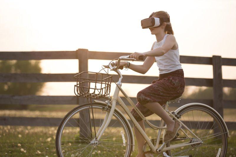 VRヘッドセットを付けて自転車に乗るイメージ
